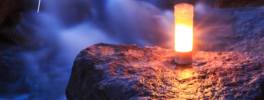 photo of a candle on a rock